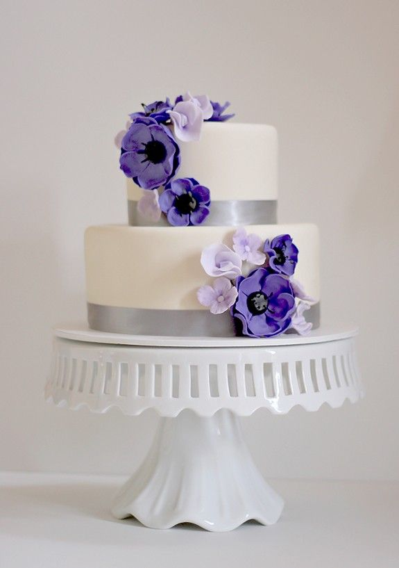 Two tier wedding cake. Small and simple. White cake with purple, indigo and white flowers with silver ribbon lining both cakes.