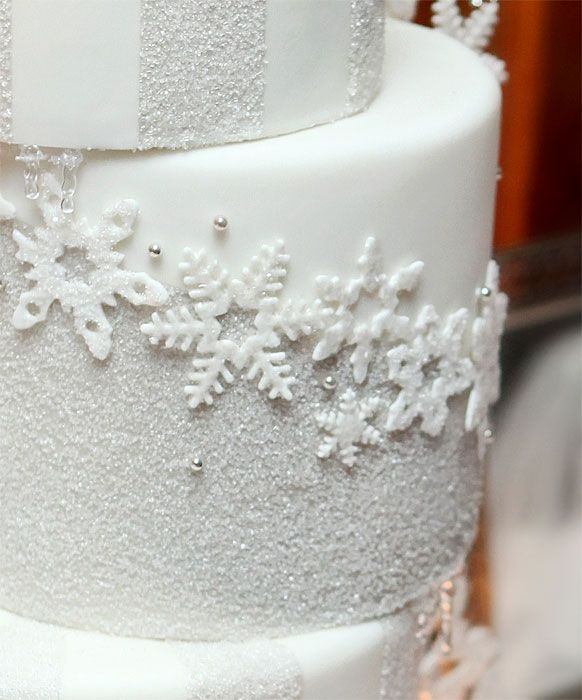 Silver Snowflake - Kristine and Derek wanted to embrace the season with their reception decor, and consequently, their cake. We took this as our opportunity to load up on edible glitter, sanding sugar and crystals. Each of the unique, handcut snowflakes was coated with edible glitter. The rest of the cake was color blocked between pale silver sugared areas and matte white fondant. To finish the look, we hung tiny icicles from the underside of the exposed cake plates. Getting chilly j