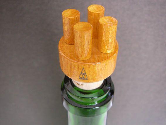 見てお分かりかと思いますが、ワインやシャンパン等に使うボトルキャップになります。コルクの上に、木を加工した4本の円柱がデザインされた形状で、使わない時は逆さにして置く事も出来ました。  CO025Y-2ボトルに、栓をしてみました。 こうすると、ボトルがボディで、何か帽子を被った人の様に見えてきます。  デザイナーは、このTWERGIシリーズが好きだったエットレ・ソットサス。   TWERGIシリーズは、生産中止になった作品が多く、その為に使用している木材や何種類有ったか等が分からない事が多いです。 CO025Yも、サイズはφ3.0cm×H5.5(コルクはφ2.0cm×H2.4cm)ですが、その他は分かりませんでした。