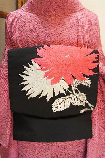 コーラルピンク美しく映えるダリアのような大輪の花模様が織り出された名古屋帯です。