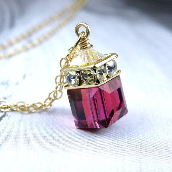 Precioso rojo rubí Swarovski cristal cubo lámpara colgante cuelga delicadamente en una cadena de oro k llena 14. Una corona de diamantes de imitación de cristal de Swarovski acentúa la parte superior para añadir brillo. Hecho a mano con 14 k de oro lleno de cable, cadena y broche de langosta. Este collar de cubos magenta de Swarovski imita el color de una piedra preciosa rubí. El pequeño regalo perfecto para una mujer nacida en julio. Ruby es su piedra. ********** Detalles del collar…