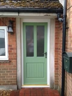 Thorncliffe timber entrance door with a white frame and cill & place green sash. Door features satin bronze handle and Arena obscure glass.