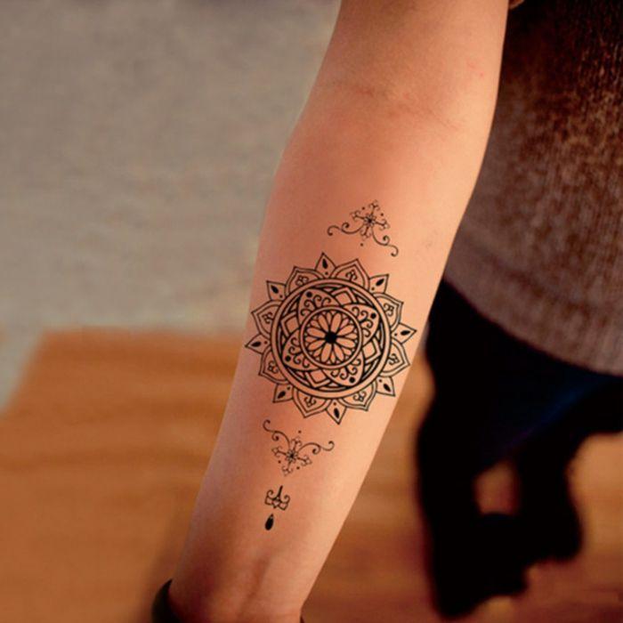 junge Frau mit Mandala Tattoo am Unterarm, kleines Tattoo amUnterarm mit Mandala