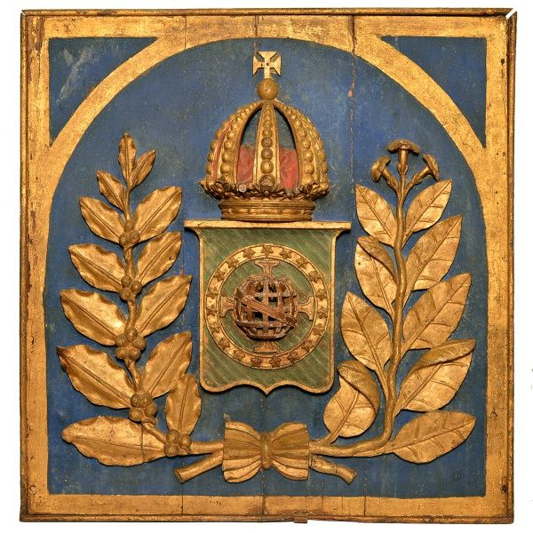 Brasão do Império do Brasil. Executado em madeira esculpida. policromada e dourada. Cerca de 1860. Medidas 74 x 77 x 14 cm