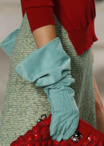 Soft blue suede gloves that settle in folds at the wrist and flare out at the forearm.  Matched with a deep red sweater & purse, and a tweed skirt