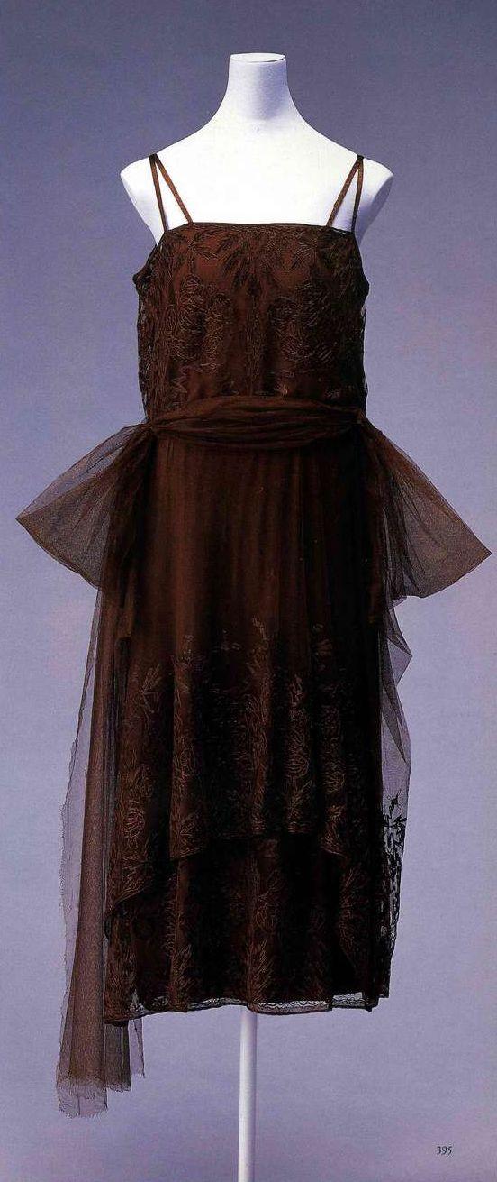 Вечернее платье. Габриэль Шанель, около 1920. Коричневый шелк шармёз под шелковым тюлем с вышитым цветочным узором, похожий на шарф пояс-украшение чуть ниже талии, двухслойная юбка, силуэт «юла».