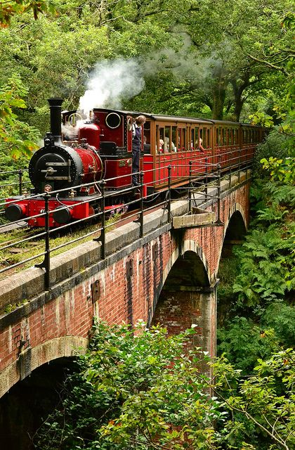 Talyllyn Railway, Wales, UK - Talyllyn Railway locomotive 'Dolgoch' crosses the viaduct after which she is named at the head of the 14.00 Tywyn Wharf-Nant Gwernol service. 0-4-0 'Dolgoch' was built in 1866 by Lowca (Cumbria) firm Fletcher Jennings. The crimson lake livery is temporary because the 2ft 3in gauge locomotive will soon require her 10-year boiler exam. Note the female fireman.