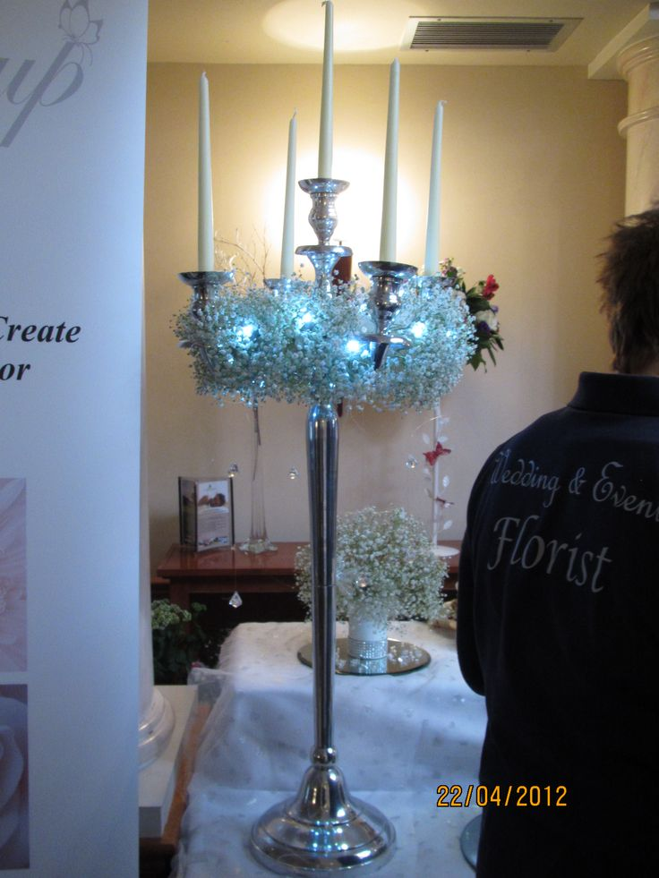 Candleabra with baby's breath and fairy lights - beautiful for a Winter wedding! www.buttercupflowers.co.uk