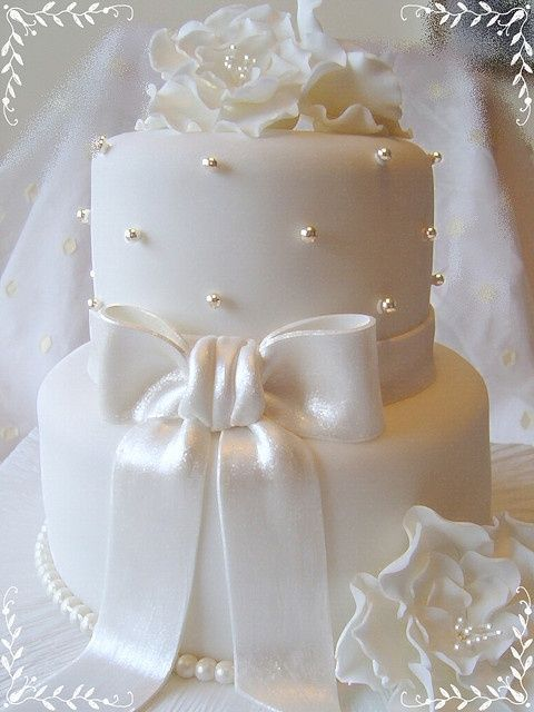 I love the simplicity and romantic look of this two tier wedding cake. All white, pearls, bow, and flowers. Ultra classy.