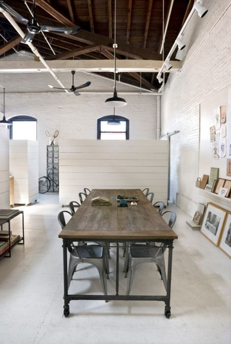White office, shiplap walls, concrete floors, metal chairs, exposed beam ceiling, painted brick walls