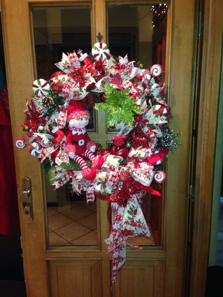 Christmas door wreath.   Base artificial greenery wreath. Added ribbon strips, large bow. Next poinsettia flower head, christmas ornaments, christmas candy, floral picks, pinecones, apples, red cardinal bird, butterflies, santa's boots, red deer and plush elf.  More you can find at https://www.facebook.com/Moje-vence-995508700482994/