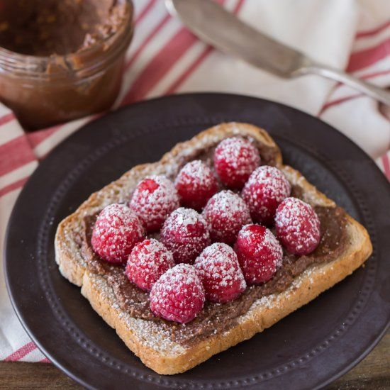 Homemade chocolate hazelnut spread on toast with fresh raspberries and ...