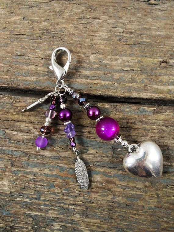 Purple Bag Charm handmade by reccabella ------------------------------------------------------------- This purple bag charm is really cute. I have used a tibetan silver heart charm as the main bead and smaller charms such as a key and feather. I have used beads in shades of purple to make