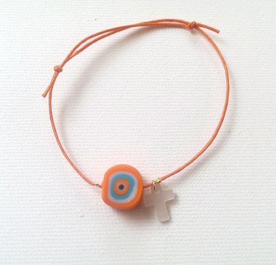 Bracelet decorated with handmade polymer clay evil eye and a shell cross.  Baptism, Christening.
