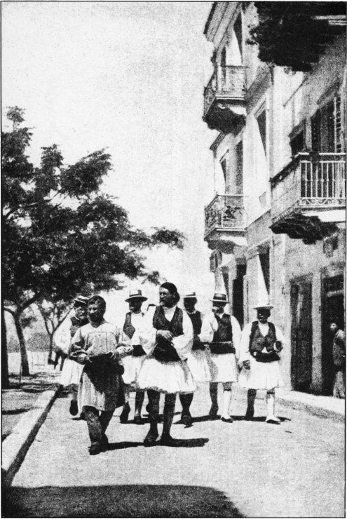 GREEK MANHOOD SWINGING DOWN THE STREETS OF NAUPLIA It is among the peasantry that the finest type of Greek manhood is found, and these Arcadians marching down a street in Nauplia well exemplify the noble bearing of the rural population. Straw hats are tending to replace the once universal red cap, but the short white kilt, or fustanella, is still the general wear, girt round by a gay sash and topped by a zouave jacket and full-sleeved shirt
