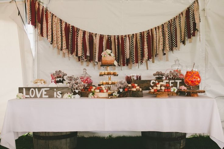 Love is Sweet - rustic tent wedding sweets table.  Barn wood signs, ripped fabric bunting and barrels.