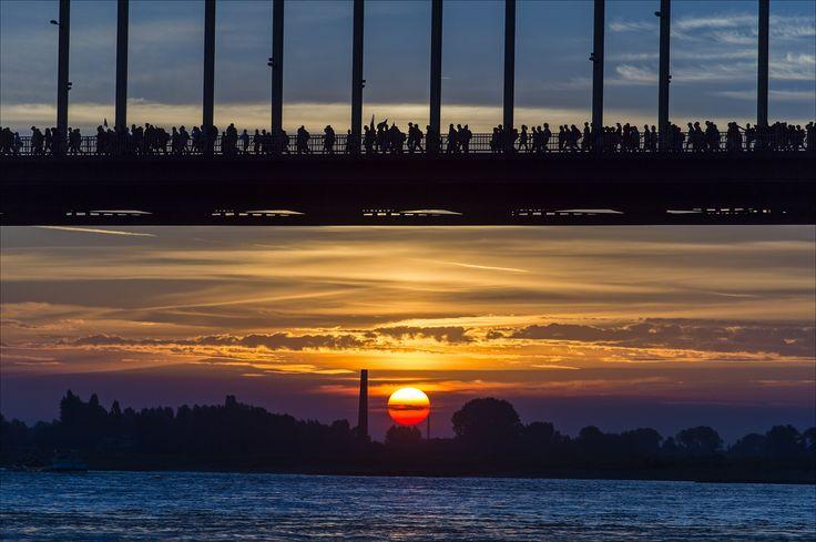 """Warga menyeberangi Sungai Waalbrug saat matahari terbenam dalam acara tahunan """"Vierdaagse"""" di kota Nijmegen, Belanda."""