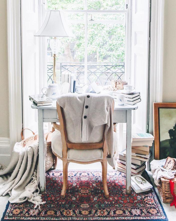 Melhor que Comprar Livros - home office neutro com cadeira acolchoada com vários livros em volta - foto por jo_rodgers no instagram