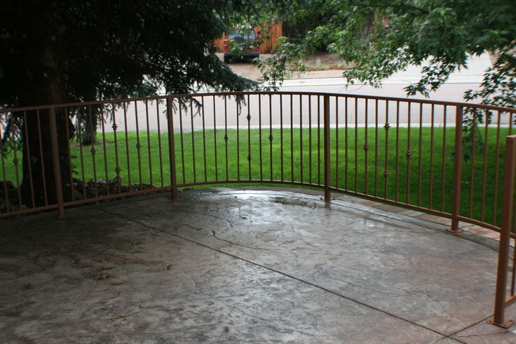 Patio with colored stamped concrete and rod iron railing for Concrete patio railing