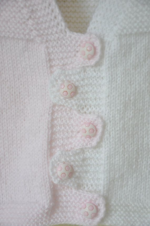This is a hand knitted baby vest.  -Made out of wool yarn.  -Five pink-white…