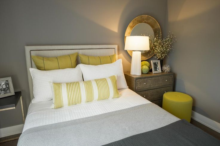 A white nightstand lamp provides a cheery glow to the gray guest bedroom.
