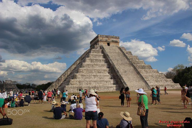 """pirâmide de Kukulkán, o Templo de Chac Mool, a Praça das Mil Colunas, e o Campo de Jogos dos Prisioneiros – podem ainda hoje ser admiradas e são demonstrativas de um extraordinário compromisso para com a composição e espaço arquitetónico. O nome Chichén-Itzá tem raiz maia e significa """"pessoas que vivem na beira da água"""". Estima-se que Chichén-Itzá foi fundada por volta dos anos 435 e 455 a.C. Foi declarada Património Mundial da Unesco em 1988."""