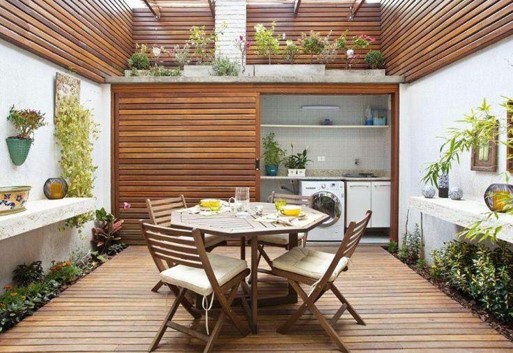 Uma bancada de concreto funciona como apoio para o preparo das refeições e acomoda também os vasos de flores. Um simples detalhe que faz a diferença na área externa!