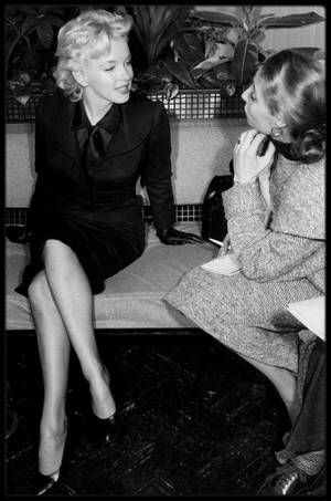 """27 Février 1956 / (Part IV) Marilyn de retour à Hollywood (après plus d'un an d'absence) est assaillie par les journalistes qui n'hésitent pas à improviser dans un des salons de l'aéroport, une conférence de presse, pour l'interroger sur son futur film en préparation, """"Bus stop"""". Le studio avait acheté les droits du film, et ce fut Joshua LOGAN, l'un des seize réalisateurs de sa liste, qui devait la diriger. Elle dut commencer le travail de pré production à la Fox le lundi 27 février."""