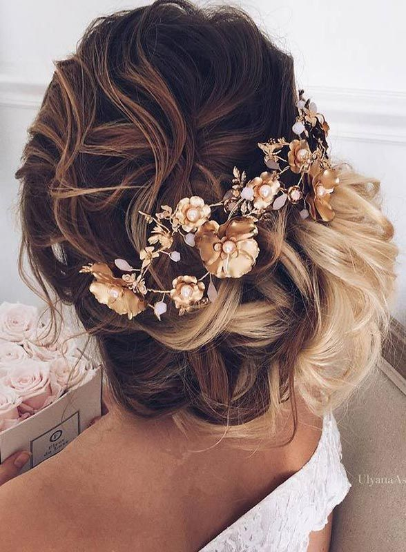 Messy has never looked this good. Flawlessly curled hair meets an entire bottle of hairspray for this fun and dramatic 'do. Add a statement piece to pull the look together (literally) and you have the most fab wedding hair. By Ulyana Aster