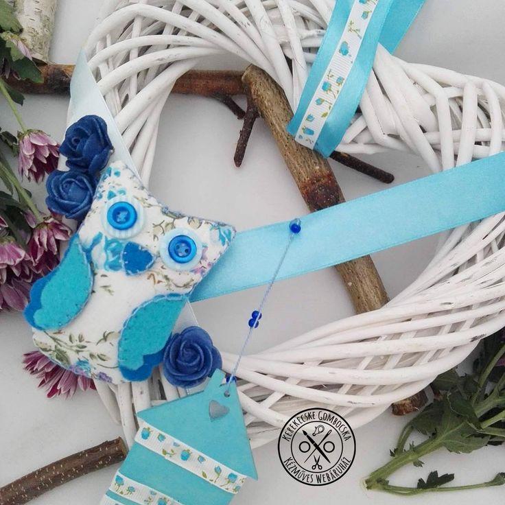 Kék-fehér, szív alakú ajtódísz bagollyal - 4190 Ft  Fonott vesszőszív koszorún visszafogott, ám mutatós dekorációs elemek: habrózsák, szatén- és mintás ripszszalagok, kézzel készült textilbagoly és fa házikó figura. Színekben harmonizáló környezetbe ajánlom bájos vendégvárónak. A koszorú mérete: 22×24 cm