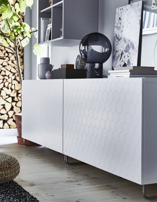26fe0f0975e A low white storage unit with honeycomb-patterned door.