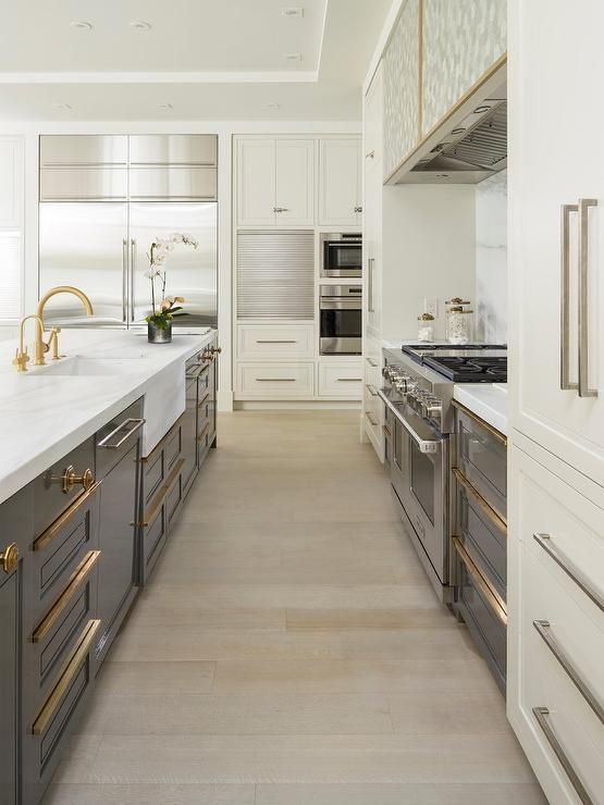 Stunning gray and ivory contemporary kitchen boasts a gray island outfitted with gray shaker cabinets accented with brass pulls and white marble countertops fitted with an apron sink and a brass gooseneck faucet.