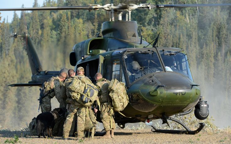 """Members of the RCMP Emergency Response Team and police dog """"Taz"""", prepare to board a Canadian Forces CH-146 Griffon helicopter from 400 Tactical Helicopter Squadron, Borden, ON, during a CF assistance to RCMP scenario in Tsiigehtchic, NT, on Operation NANOOK 2012. Photo credit: Sgt Frank Hudec, Canadian Forces Canada Command © 2012 DND-MDN Canada #StrongProudReady"""