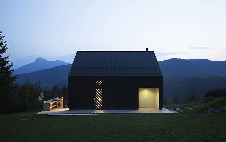 the black, monolithic building at daytime turns into a lantern-like nest during the evening, casting light on its surroundings.