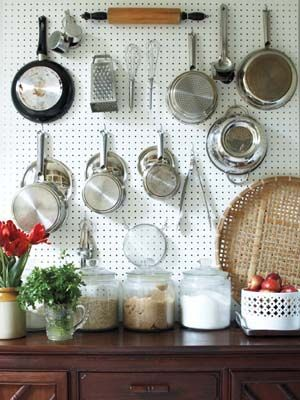 Straight from the hardware stores, sheets of pegboard create functional, yet chic storage space in a kitchen.