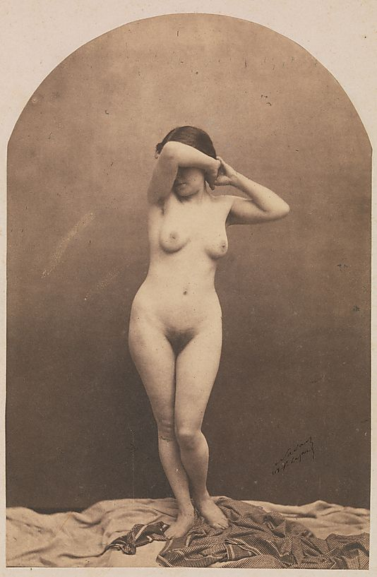 "THE MET ""Naked before the camera"" [Standing Female Nude]  Standing Female Nude]  Nadar  (French, Paris 1820–1910 Paris)  Date: 1860–61 Medium: Salted paper print from glass negative Dimensions: Image: 20.2 x 13.3 cm (7 15/16 x 5 1/4 in.) Classification: Photographs Credit Line: Purchase, The Horace W. Goldsmith Foundation Gift, through Joyce and Robert Menschel, 1991 Accession Number: 1991.1174"