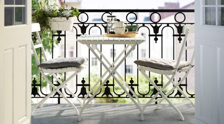 White outdoor table and chairs on a balcony with a wrought iron railing.