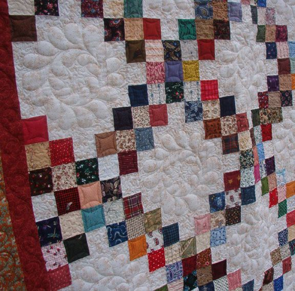 A Double Irish Chain quilt. I like the quilting pattern she used inside the large white patch.