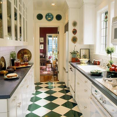 A classic checkerboard tile design -- updated by a green-and-white color scheme -- adds dimension to the floor and can make small kitchens seem larger. Galley kitchens can get big style upgrades through attention to detail. Here, glass-front doors and glass knobs combine with white cabinets for a vintage look. Note how the counter opposite the sink is kept open for maximum use.