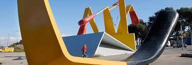 """Claes Oldenburg firma esta monumental obra junto con su esposa, Coosje van Bruggen, la escultura es una caja de cerillas; la más alta de ellas, de 20 metros de altura, representa estar encendida y fue instalada con motivo de los Juegos Olímpicos.  Escogieron los colores rojo y amarillo porque encajaban perfectamente con las cerillas y también, porque """"son los colores que se hallan en la bandera catalana""""."""