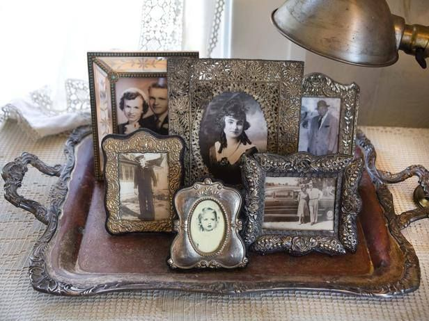 An old serving tray makes a wonderful place to group small vintage framed photos.