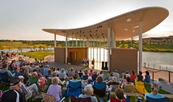 Designed by HGA Architects and Engineers, Town Green is an open-air community band shell for music, dance and theater under a dramatic concrete canopy.