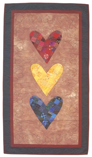 "For this trio of folk-art hearts, Sandy Bonsib created pieced fabric from 2"" squares, then cut the hearts from the fabric and appliquéd them to a background. So simple and quick—and so charming!"