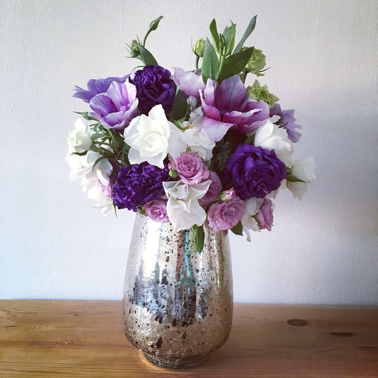 DIY flower arrangement: Spring/Summer wedding centerpiece in purple, lilac, and white. Anemones, carnations, and spray roses in a gold mercury vase.