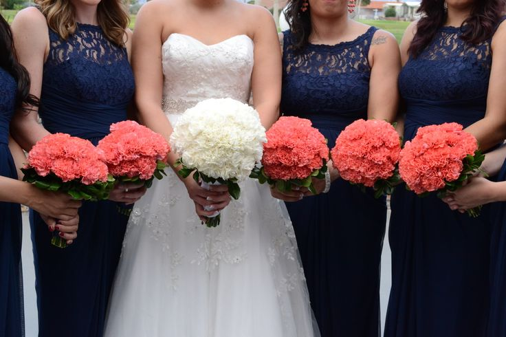 Weddings - Bridesmaids have coral carnation bouquets, bride has a white carnation bouquet.