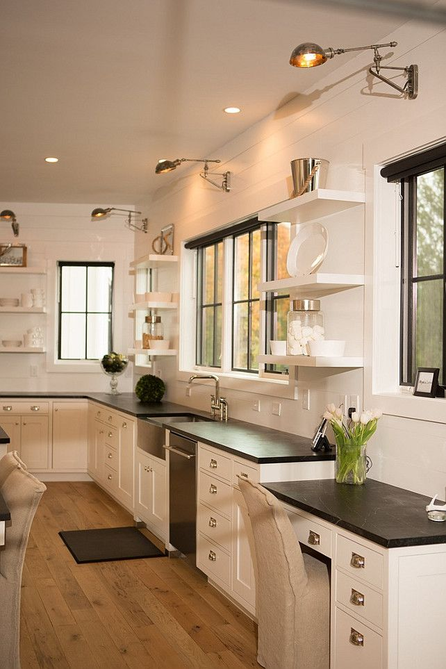 Kitchen Desk. Soapstone kitchen desk. This kitchen features shiplap walls lined with white cabinets paired with soapstone countertops fitted with a stainless steel apron sink under a window flanked by stacked floating shelves. Kitchen with a drop down soapstone top desk placed under a window illuminated by a swing arm sconce. #Kitchen #Desk #KitchenDesk Hahn Builders.