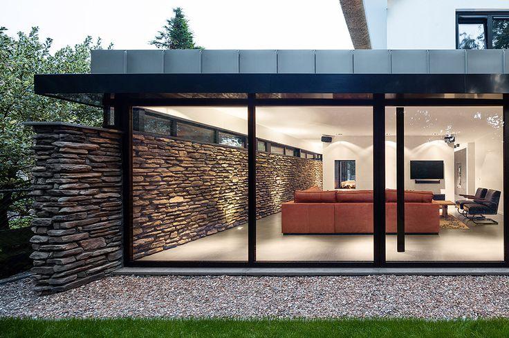 Moderne woonkamer met gietvloer, natuursteen muur, zinken dak en aluminium kozijnen. Een rand met grind ligt tegen de kozijnen aan. Ontwerp BNLA architecten, fotografie Studio de Nooyer.