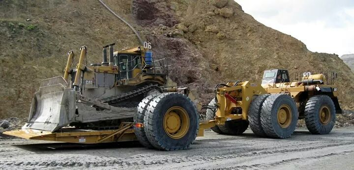 Cat 777 haul truck moving a Cat D11 on a tilt deck heavy-duty trailer. Iron moving Iron .......