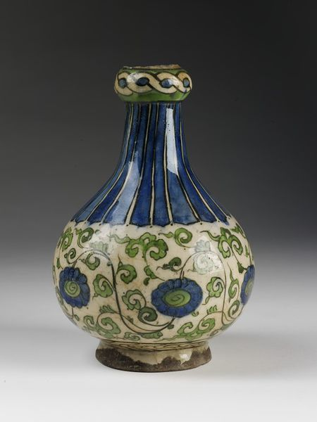 Bottle | Made in Damascus, Syria, 16th century-17th century | Materials: fritware painted under the glaze | Bottle of grey fritware, painted in colours on a white slip and covered with a clear glaze. Pear-shaped body, and with a long neck with a knop, above which has been broken off. Painted in blue and green outlined in olive-green. Round the body are flowers and scrolled foliage on a continuous wavy stem. The neck and shoulder are vertically striped | VA Museum, London