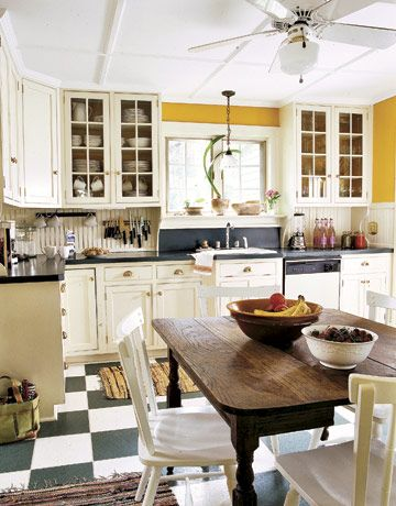 retro black/white floor, mustard walls, beautiful table, love the placement of the utensil/cup holders--Ikea?   pretty, pretty kitchen